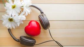 Il rilassamento e accogliente con cuore ascoltano musica e margherita su di legno Immagini Stock