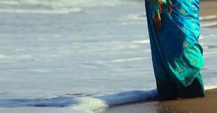 Il rilassamento felice della donna sulla spiaggia soleggiata del mare sotto il cielo di luce solare con le nuvole al giorno di es Fotografia Stock Libera da Diritti