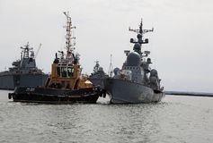 Il rimorchio spinge la nave da guerra nell'area dell'acqua di porto di Baltiysk Fotografia Stock