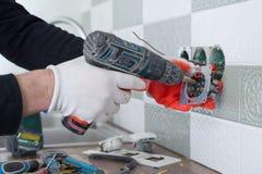 Il rinnovamento e la costruzione in cucina, primo piano degli elettricisti passano l'installazione dello sbocco sulla parete con  immagine stock libera da diritti