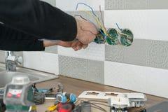 Il rinnovamento e la costruzione in cucina, primo piano degli elettricisti passano l'installazione dello sbocco sulla parete con  fotografia stock libera da diritti
