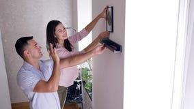 Il rinnovamento nelle coppie piane e felici avvita lo scaffale con il cacciavite e la pittura d'attaccatura sulla parete dopo la  stock footage