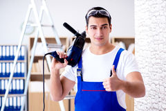 Il riparatore che lavora con il perforatore del trapano di perforazione Fotografia Stock