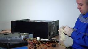 Il riparatore del computer ha messo i guanti protettivi sulle mani Cassa e componenti del computer archivi video