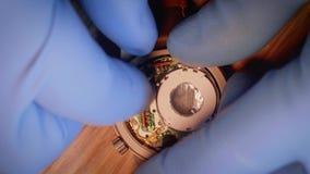 Il riparatore dell'orologio mette il meccanismo riparato posteriore nel caso medio video d archivio