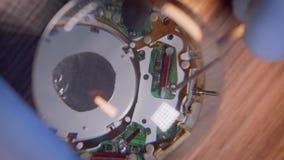 Il riparatore dell'orologio utilizza la lente di ingrandimento sotto la macchina fotografica per vedere il meccanismo dell'orolog stock footage
