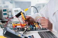 Il riparatore ripara l'attrezzatura elettronica fotografia stock
