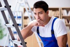 Il riparatore triste che pende contro la scala Fotografia Stock