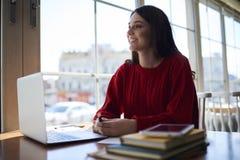 Il riposo femminile attraente sorridente del positivo durante irrompe lo spazio coworking Immagine Stock Libera da Diritti