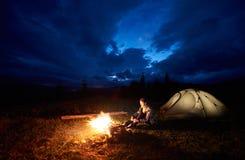 Il riposo turistico della donna alla notte che si accampa in montagne si avvicina al fuoco di accampamento ed alla tenda nell'amb fotografie stock