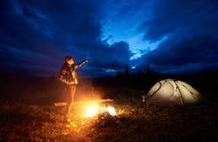 Il riposo turistico della donna alla notte che si accampa in montagne si avvicina al fuoco di accampamento ed alla tenda nell'amb immagini stock