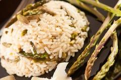 Il riso con asparago selvaggio su un piatto del blavk con la forcella è servito sulla a Fotografia Stock