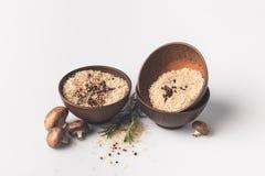 Il riso crudo con le spezie ed i funghi su bianco sorgono Fotografia Stock Libera da Diritti