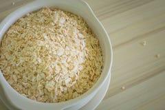 Il riso dell'avena in ciotola bianca sull'immagine di legno di tono del verme del tavolo della presidenza Immagini Stock