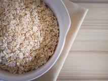 Il riso dell'avena in ciotola bianca sull'immagine di legno di tono del verme del tavolo della presidenza Immagine Stock