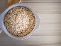 Il riso dell'avena in ciotola bianca sull'immagine di legno di tono del verme del tavolo della presidenza Fotografie Stock Libere da Diritti