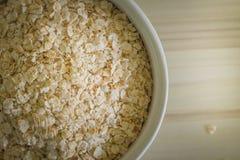 Il riso dell'avena in ciotola bianca sull'immagine di legno di tono del verme del tavolo della presidenza Fotografia Stock Libera da Diritti