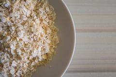 Il riso dell'avena in ciotola bianca sull'immagine di legno di tono del verme del tavolo della presidenza Immagini Stock Libere da Diritti