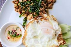 Il riso ha completato con carne di maiale in padella, basilico e l'uovo fritto Fotografia Stock Libera da Diritti
