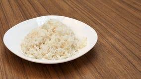 Il riso lavorato dei semi in piatto bianco ha spazio della copia Immagini Stock