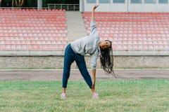 Il risolvere della ragazza afroamericana atletica che fa gli esercizi sullo stadio mentre ascoltando la musica in cuffie Immagine Stock