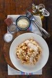 Il risotto con il galletto si espande rapidamente in piatto bianco sull'sedere di legno Fotografia Stock