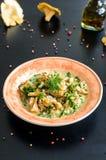 Il risotto delizioso con il galletto si espande rapidamente sopra fondo nero rustico Fotografia Stock