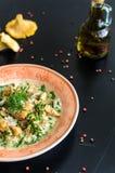 Il risotto delizioso con il galletto si espande rapidamente sopra fondo nero rustico Immagini Stock