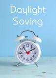 Il risparmio di luce del giorno cronometra l'orologio bianco su una tavola di legno blu dell'acqua d'annata Fotografia Stock Libera da Diritti