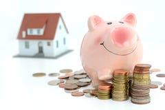Il risparmio per il bene immobile proietta con la casa ed il porcellino salvadanaio del piccolo modello che scalano sui mucchi de Immagini Stock