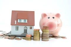 Il risparmio per il bene immobile proietta con la casa ed il porcellino salvadanaio del piccolo modello che stanting sui mucchi d Immagini Stock