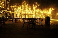 Il ristorante vuoto di notte, il lotto delle tavole e le sedie senza una, luci leggiadramente magiche sugli alberi gradiscono la  Immagine Stock Libera da Diritti