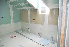 Il ritocco del bagno della soffitta con la riparazione del muro a secco, intonacante la pittura, stucco Riparazione e rinnovament fotografia stock