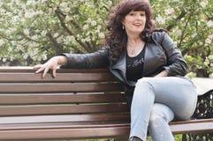 Il ritratto all'aperto della donna di medio evo sta sedendosi su una pietra Immagini Stock