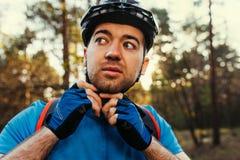 Il ritratto alto vicino del ciclista serio e premuroso chiude il casco protettivo all'aperto e distogliendo lo sguardo, pensante  fotografia stock