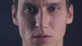 Il ritratto alto vicino del giovane apre i suoi occhi e sguardi fissi nella macchina fotografica su un fondo nero archivi video