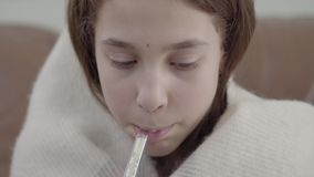 Il ritratto alto vicino dell'adolescente avvolto in una coperta prende un termometro nella sua bocca e misura la temperatura archivi video