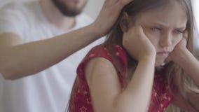 Il ritratto alto vicino della bambina triste che si siede sulla priorità alta che tiene la sua testa in mani si chiude su Il padr archivi video