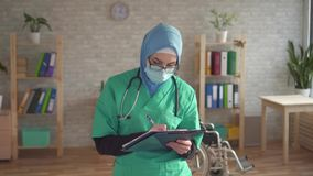 Il ritratto alto vicino di un medico femminile è una donna musulmana con una cartella video d archivio