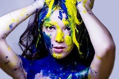Il ritratto alto vicino modo/di bellezza della donna ha dipinto blu e giallo su fondo bianco Immagini Stock
