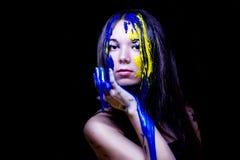 Il ritratto alto vicino modo/di bellezza della donna ha dipinto blu e giallo su fondo nero Fotografie Stock