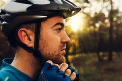 Il ritratto alto vicino nel profilo del ciclista bello e serio chiude il suo casco protettivo all'aperto e distogliendo lo sguard immagini stock libere da diritti
