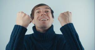 Il ritratto Amazed ha sorpreso il giovane in maglione nero su fondo bianco Vittoria o successo improvvisa Concetto di vittoria video d archivio