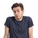 Il ritratto anteriore di un giovane che dubita scrollare le spalle mette Fotografia Stock Libera da Diritti