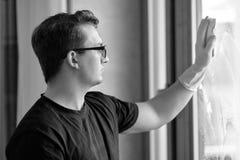 Il ritratto in bianco e nero di giovane uomo caucasico bello lava la finestra con la spugna Capelli ricci scuri, vetri, sguardo a immagine stock