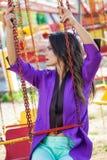 Il ritratto castana caucasico della donna di giovane modo si siede sul carosello volante di estate del parco di divertimenti immagine stock libera da diritti