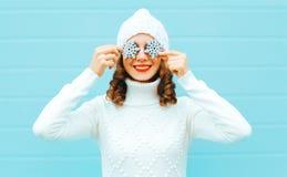 Il ritratto che la donna sorridente felice tiene i fiocchi di neve chiude il suo occhio immagine stock libera da diritti