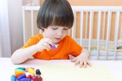 Il ritratto dei 2 anni adorabili di pitture del ragazzo con la cera disegna a matita Fotografia Stock