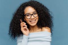 Il ritratto dei colloqui afroamericani soddisfatti della donna sul telefono cellulare, gode della conversazione piacevole, dice l fotografia stock libera da diritti