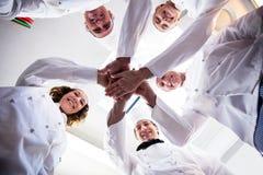 Il ritratto dei cuochi unici team un le mani ed incoraggiare Fotografia Stock